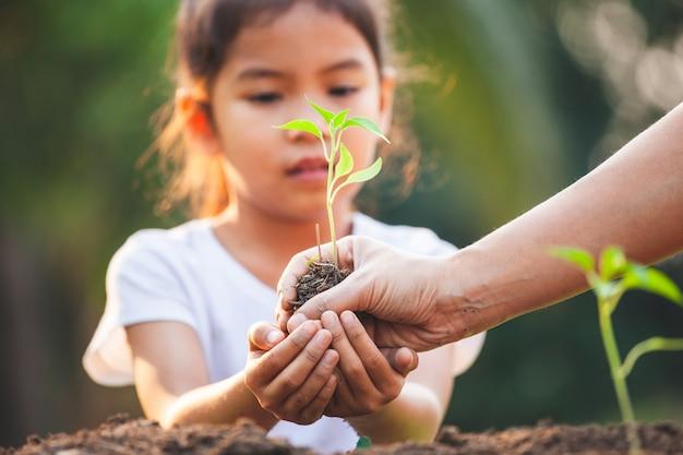 Милая азиатская девушка ребенка и родитель засаживая молодые саженцы в черной почве совместно в саде