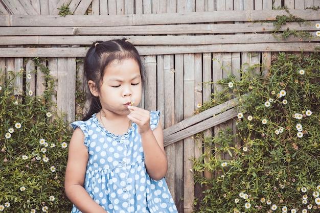 Симпатичные азии девочка девочка дует маленький цветок в саду с удовольствием в старинный цветовой тон