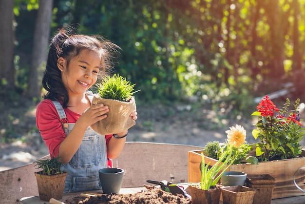 かわいいアジアの子供の女の子は植物の世話をします。家でガーデニングをしている娘。春の日の人々の自然の概念で幸せな休日の家族。