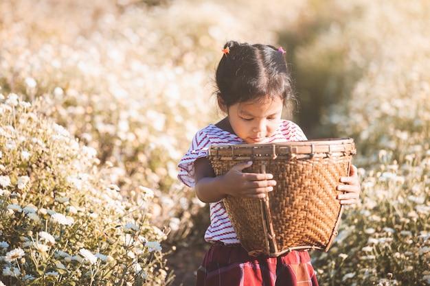 幸せで花畑で美しい花のバスケットを運ぶかわいいアジアの子供の女の子