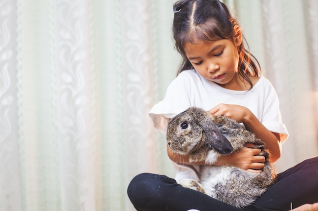 Cute asian child girl carrying and playing with cute holland rabbit with love and tenderness at easter festive