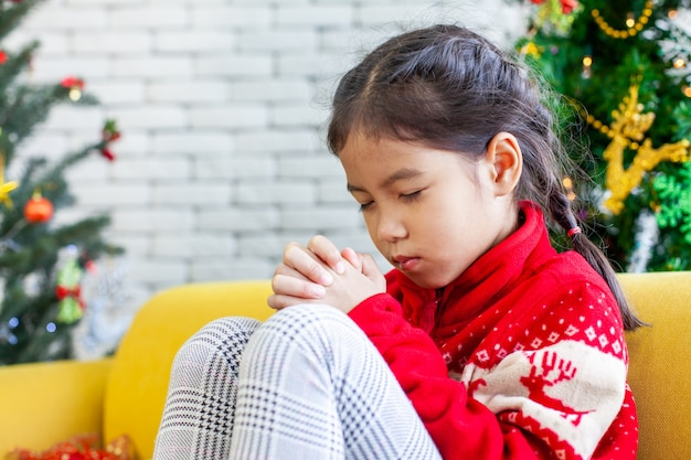 Cute asian child girl closed her eyes and folded her hand in prayer to wish in christmas celebration
