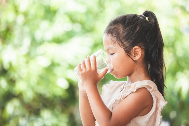 Cute asian child girl drinking fresh water from glass