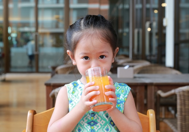 Cute asian child girl drinking orange juice at restaurant with looking camera.