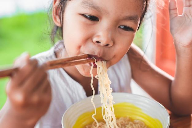 Симпатичная азиатская девочка, едят вкусные лапши быстрого приготовления с палочками для еды