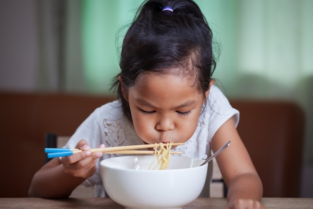 Cute asian child girl eating delicious instant noodles with chopsticks