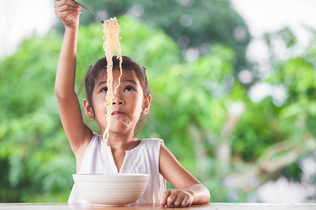 Симпатичная азиатская девочка, едят вкусные лапши быстрого приготовления с вилкой