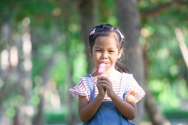 공원에서 아이스크림을 먹는 귀여운 아시아 아이 소녀