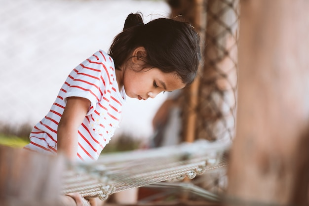 Cute asian child girl having fun to climb and play in the playground with happiness