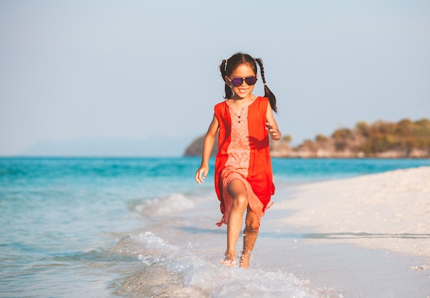 Cute asian child girl having fun to play and run on beach near the beautiful sea in summer vacation