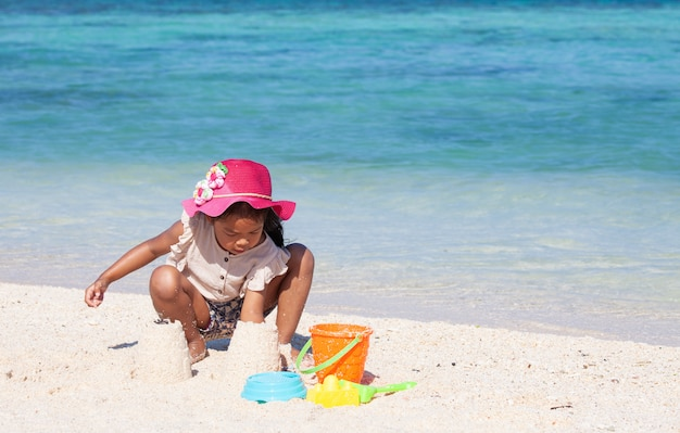 Cute asian child girl having fun to play with sand on beach in summer vacation