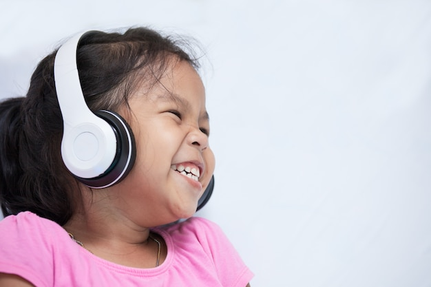 Cute asian child girl in headphones listening to music