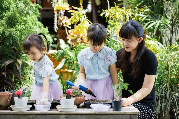 Милая азиатская мать порции девушки ребенка засаживая или cutivate заводы в саде.