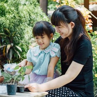 庭に植物を植えるまたはcutivateする母親を助けるかわいいアジアの子女の子。