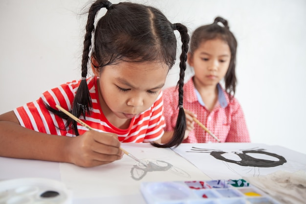 Cute asian child girl and her sister doing homework brushing and painting their picture with watercolor together