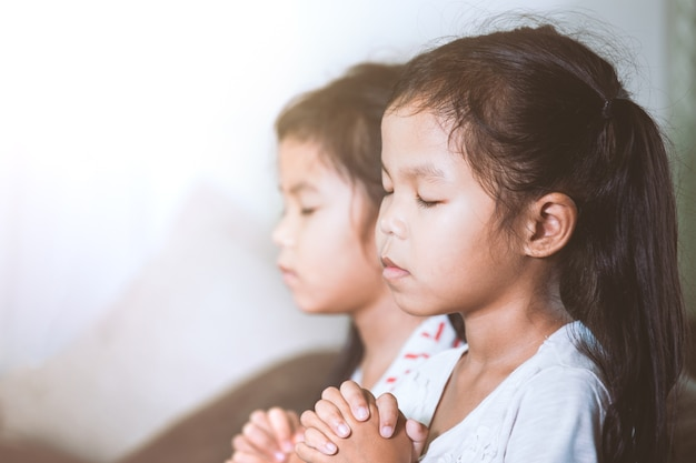 Cute asian child girl and her sister praying with folded her hand in the room together