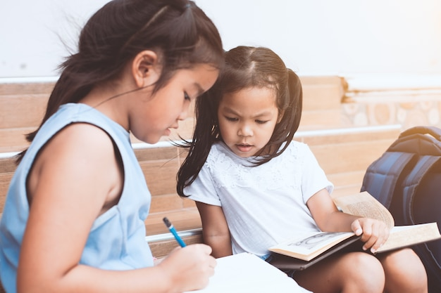 Cute asian child girl and her sister reading a book  together with fun and happiness