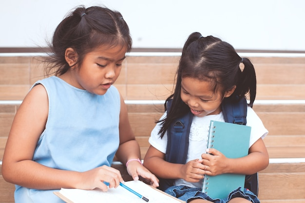 Cute asian child girl and her sister reading a book  together