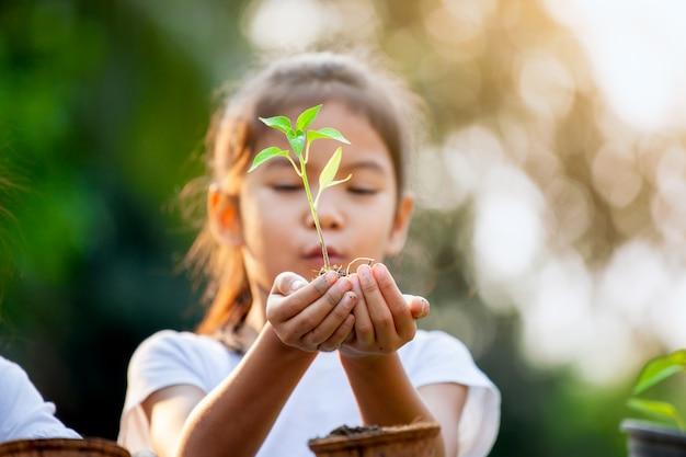 Милая азиатская девушка ребенка держа молодое дерево для засаживать в рециркулированных баках волокна в саде с потехой
