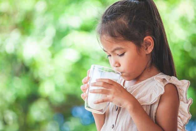 Cute asian child girl is drinking a milk from glass
