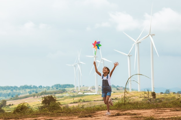 Cute asian child girl is running and playing with wind turbine toy in the wind turbine field