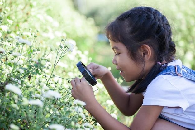 Милая азиатская девушка ребенка смотря красивый цветок через лупу в поле цветка