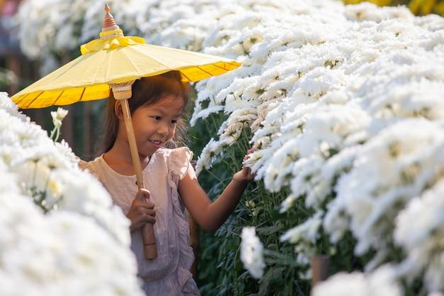 かわいいアジアの子少女は花が大好きで、花の庭で美しい花を楽しんで