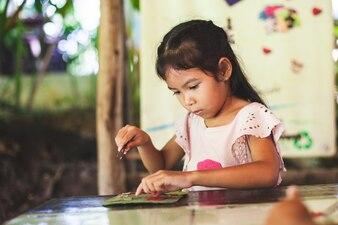 かわいいアジアの子供の女の子は、象の糞から紙をリサイクルして工芸をする