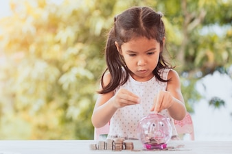 Cute asian child girl making stacks of coins and putting money into piggy bank