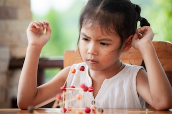 Cute asian child girl playing and creating with play dough and toothpick.