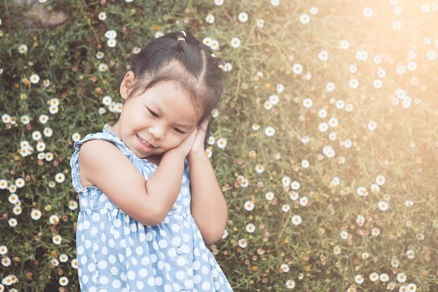 Симпатичная азиатская девочка, играющая в саду с удовольствием в старинном цветовом тоне