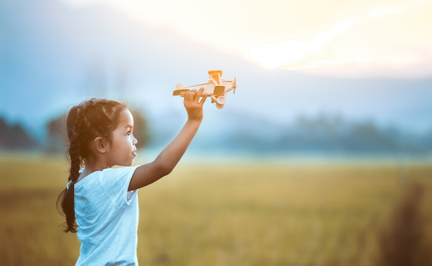 Cute asian child girl playing with toy wooden airplane in the field at sunset time