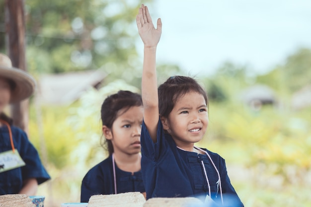 Cute asian child girl raising her hand in the air to answer the question in the classroom