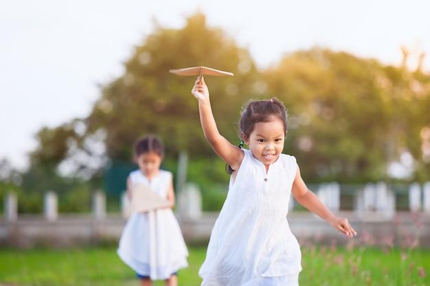 かわいいアジアの子供の女の子、実行して、ヴィンテージの色調のフィールドでおもちゃの紙飛行機を再生