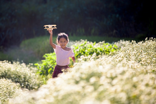 Cute asian child girl running and playing with toy wooden airplane in the flower field