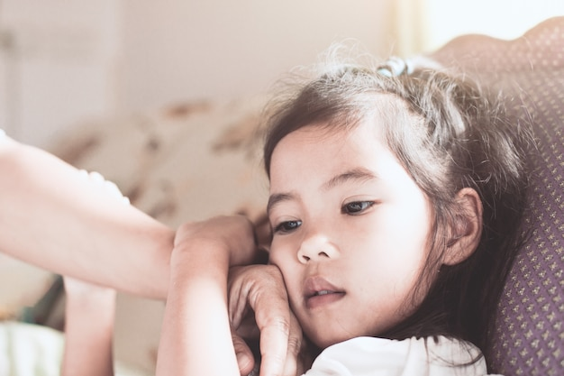 Cute asian child girl sickness and mother hand touch her face to check temperature with love and care