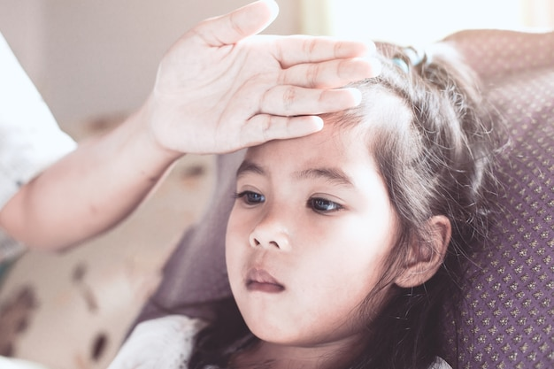 Cute asian child girl sickness and mother hand touch her forehead to check temperature with love and care
