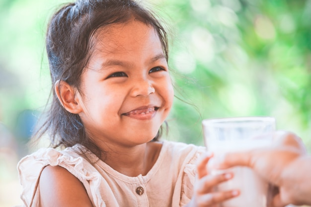Cute asian child girl smiling when get a glass of milk from her mother
