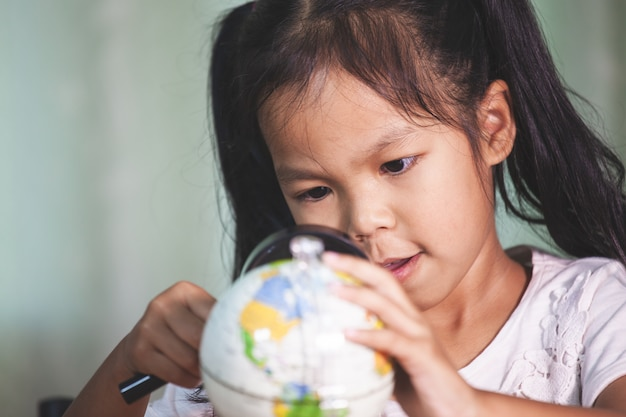Cute asian child girl use magnifier to look and study at the globe in classroom