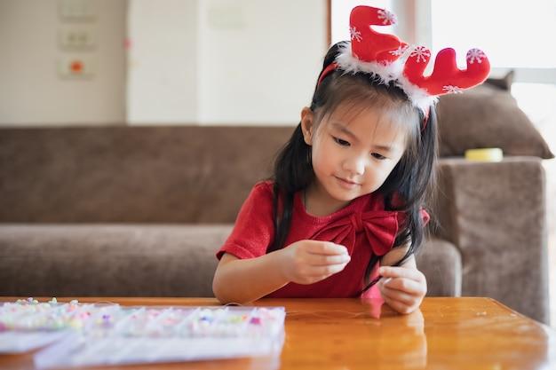 가정에서 의도와 재미와 문자열에 구슬 스레딩 크리스마스 의상을 입고 귀여운 아시아 아이 소녀.