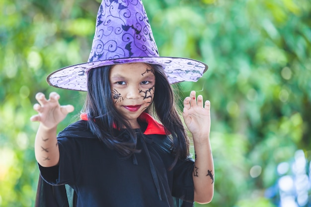 Cute asian child girl wearing halloween costumes and makeup having fun on halloween celebration