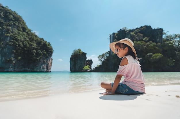 Милая азиатская девочка ребенка в шляпе и солнечных очках, сидя на пляже и играя с песком.