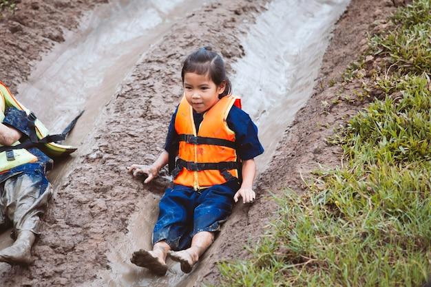 かわいいアジアの子供の女の子は、泥でスライダーを再生する楽しみを持つジャケットを着て