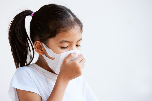 Cute asian child girl wearing protection mask to against air smog pollution