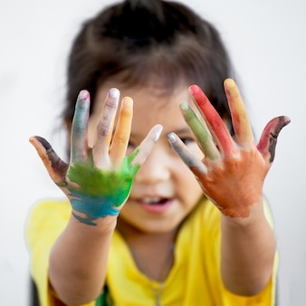 Cute asian child girl with hands painted in colorful paint on white background
