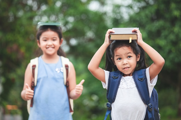 Cute asian child girl with school bag and her sister put a book on head together