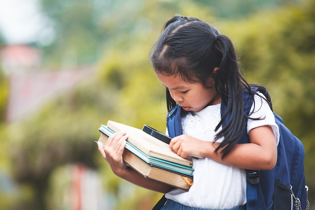 Cute asian child girl with school bag holding books and magnifying glass ready to go to sc