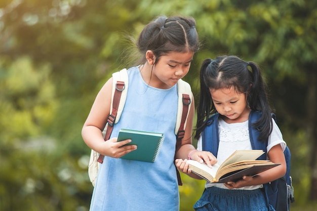 Cute asian child girl with school bag reading a book with her sister together