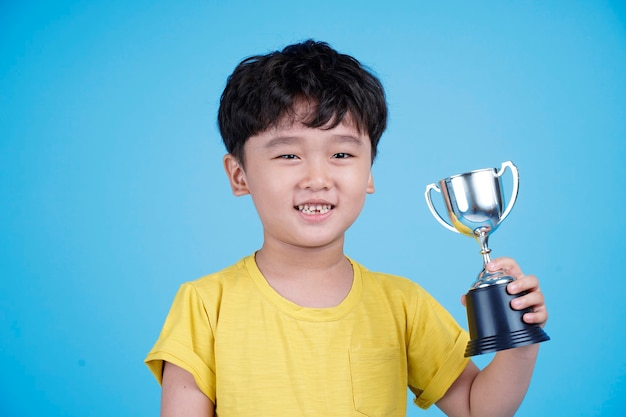 Cute asian child holding up a trophy