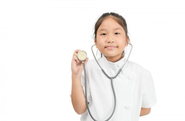 Милый азиатский ребенок в пальто доктора держа стетоскоп изолированный